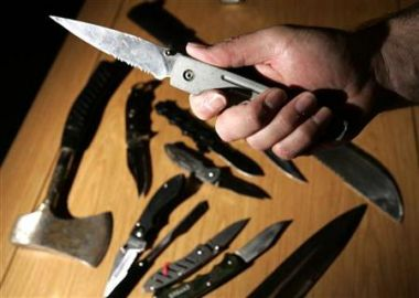 A policeman holds a lock knife over a selection of dangerous weapons ...